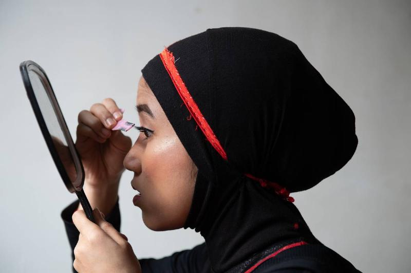A woman puts on makeup while looking in a mirror.