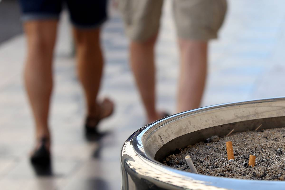 Two men walk away from a public ash tray.