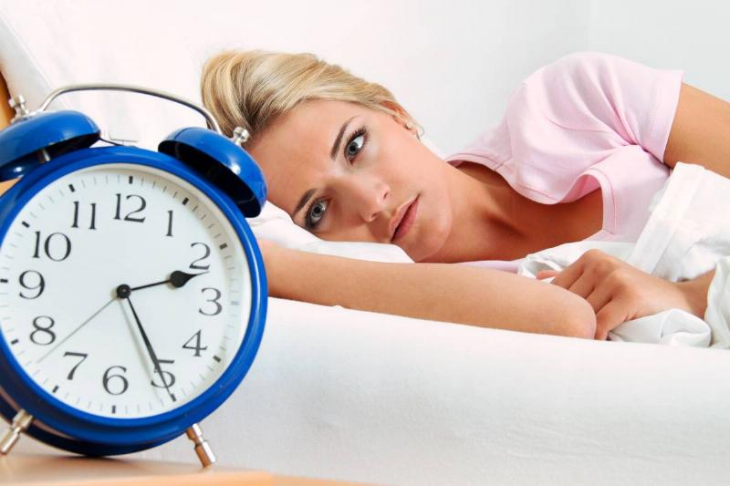 A woman lies awake in bed at two in the morning.