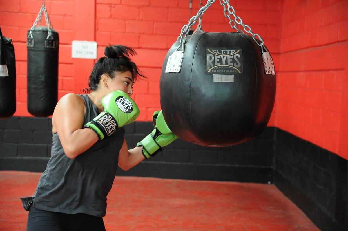 A woman boxes during a gym training session.