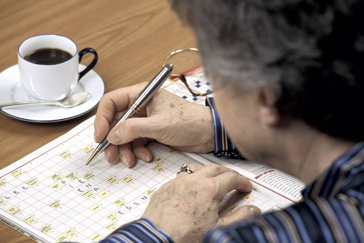 An elderly woman works on a crossword puzzle while drinking coffee.