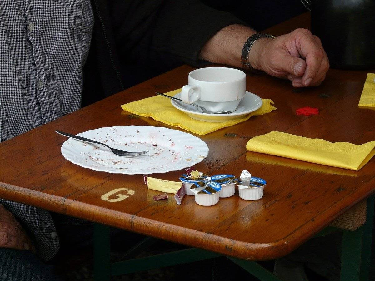 Several containers of opened coffee creamers are on a restaurant table next to coffee.