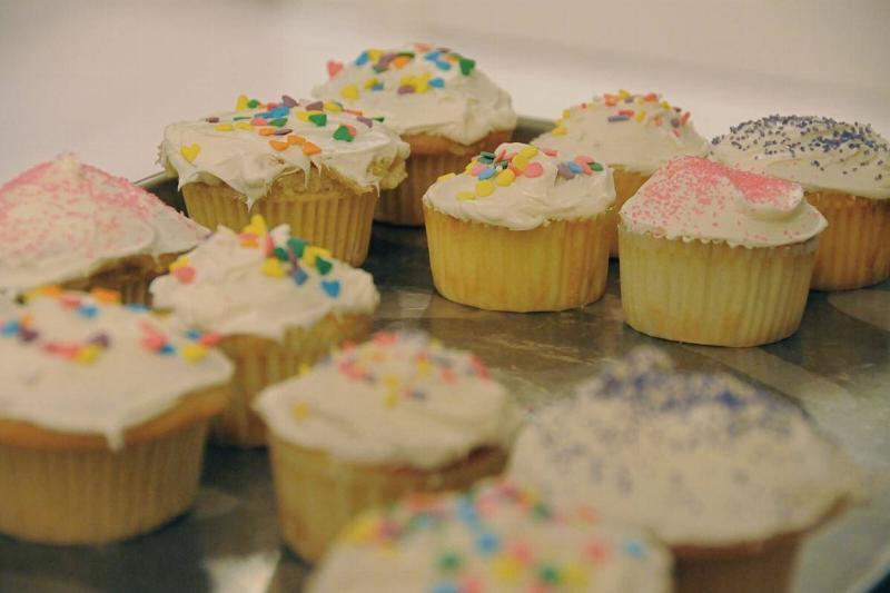 Homemade cupcakes sit on a baking sheet.