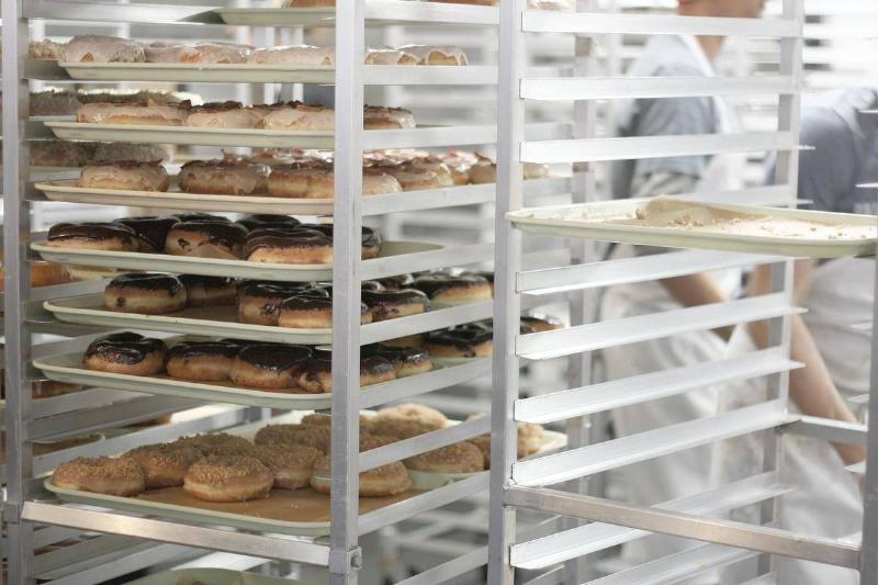 Donuts are sorted onto shelves in a bakery.