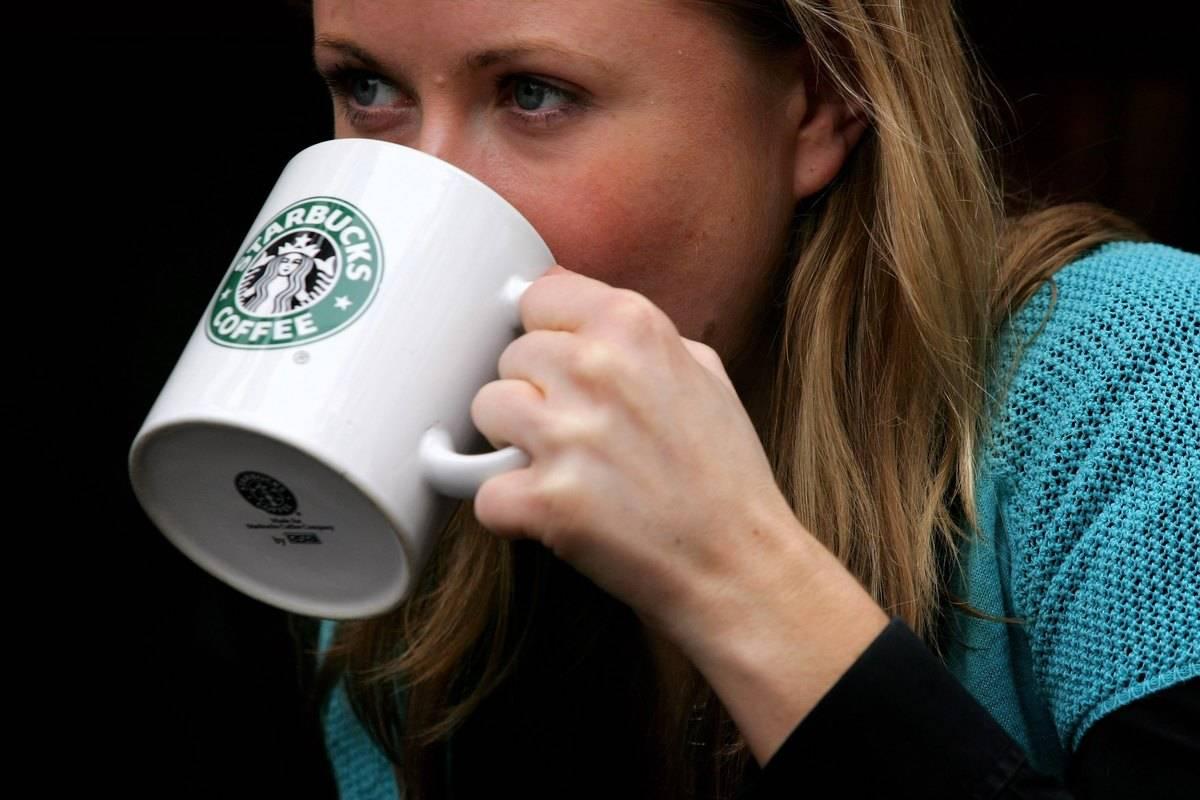 A woman drinks coffee from a Starbucks mug.