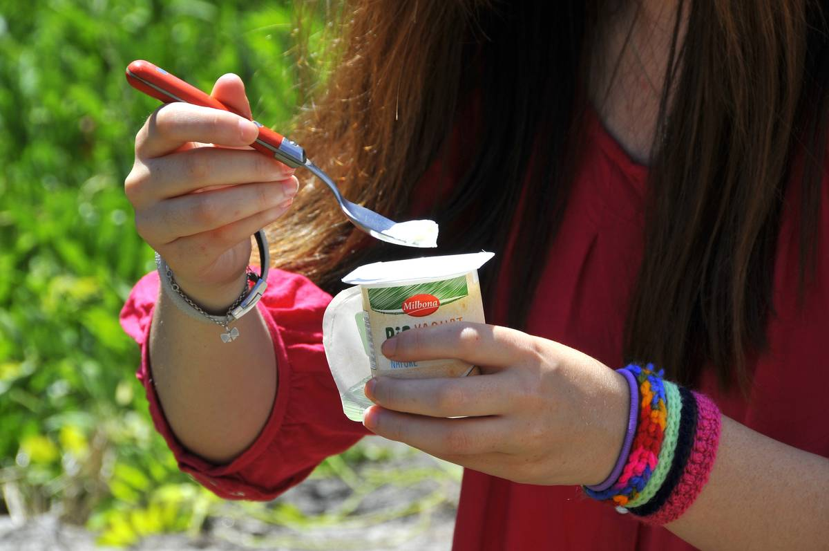 A woman takes a spoonful of yogurt out of a container.