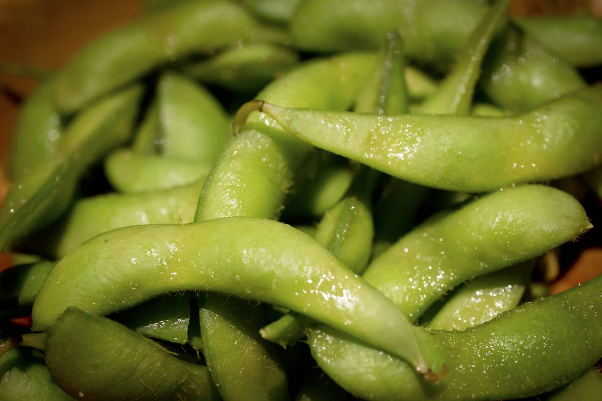 A close-up shows salted edamame.