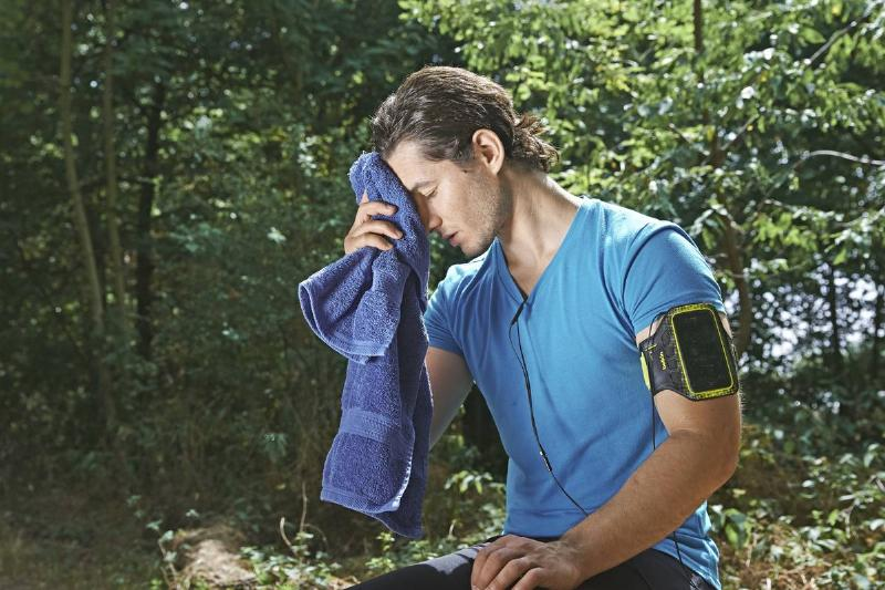 Man wiping his face after exercising