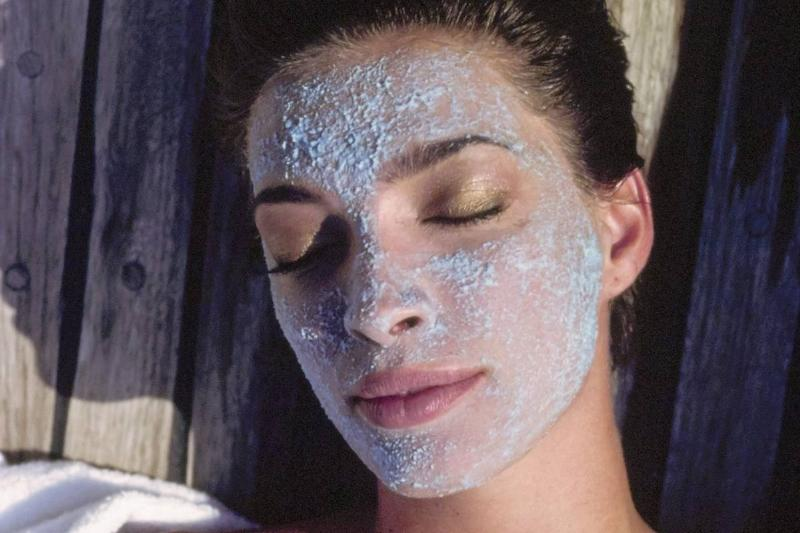 A woman lies in the sun while wearing an exfoliating mask.