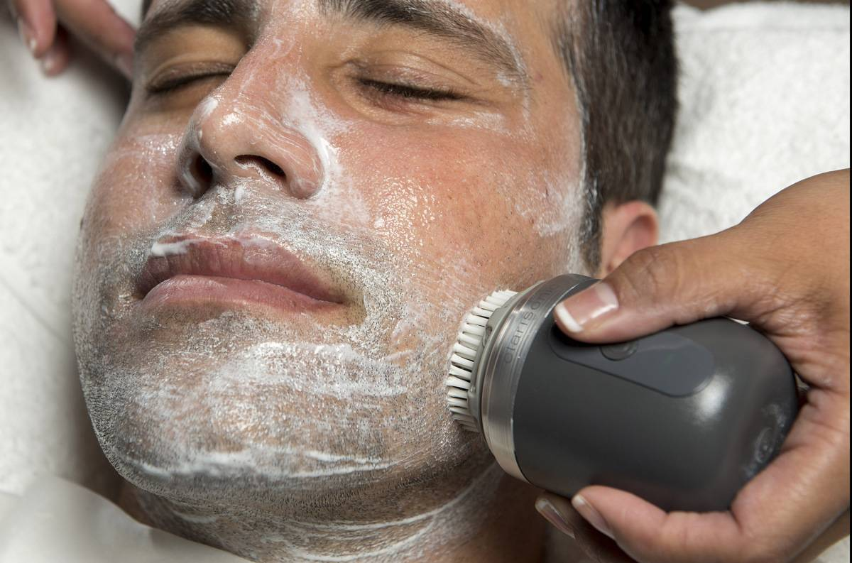 A man receives a facial with a brush that rubs exfoliator on his face.