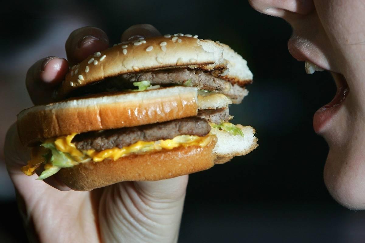 A woman eats a fast food burger.