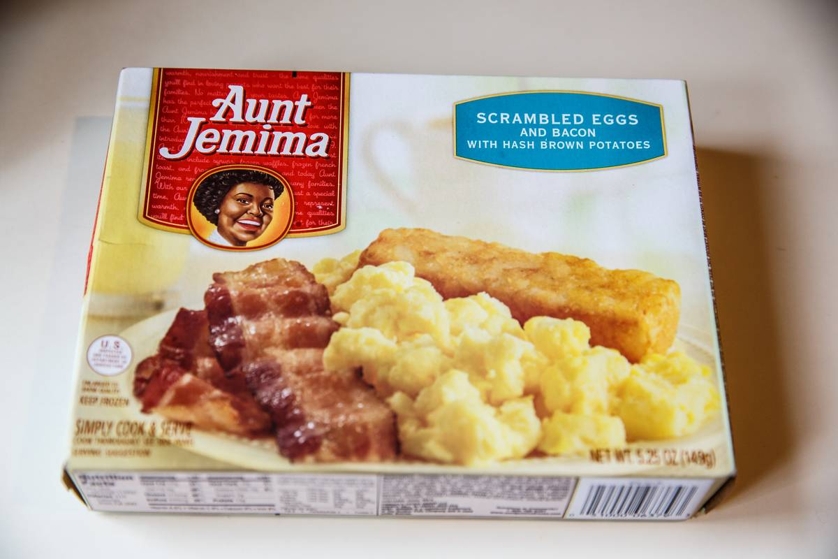 A packaged Aunt Jemima frozen breakfast of eggs and bacon lies on the table.