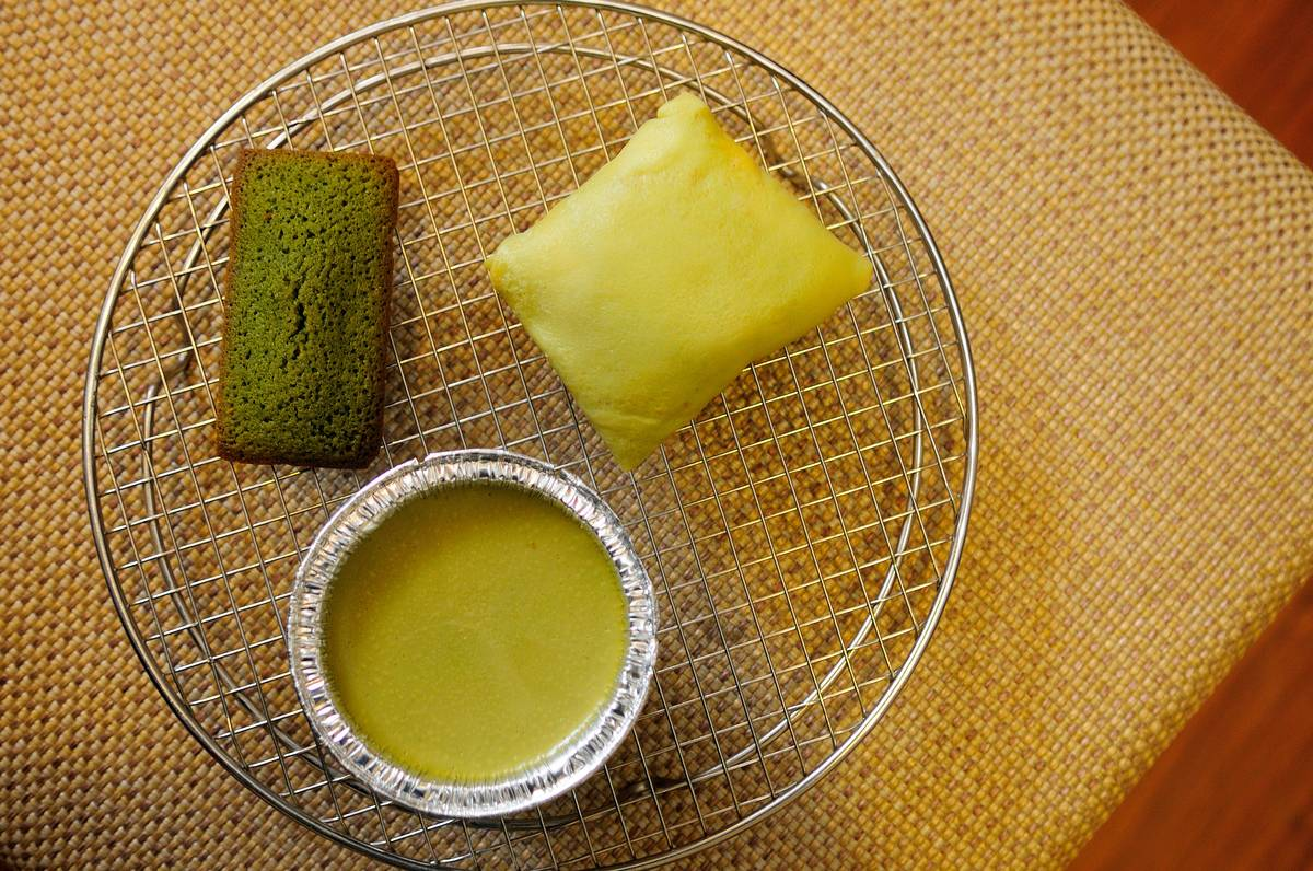 A cup of green tea sits next to two green tea-flavored baked goods on a tray.