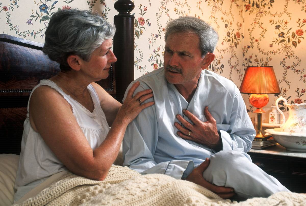 While sitting in bed, a wife comforts her husband, who is suffering from heartburn.
