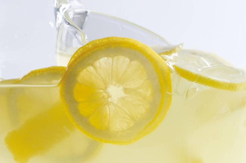 A close-up shows a straw in a glass of lemonade.