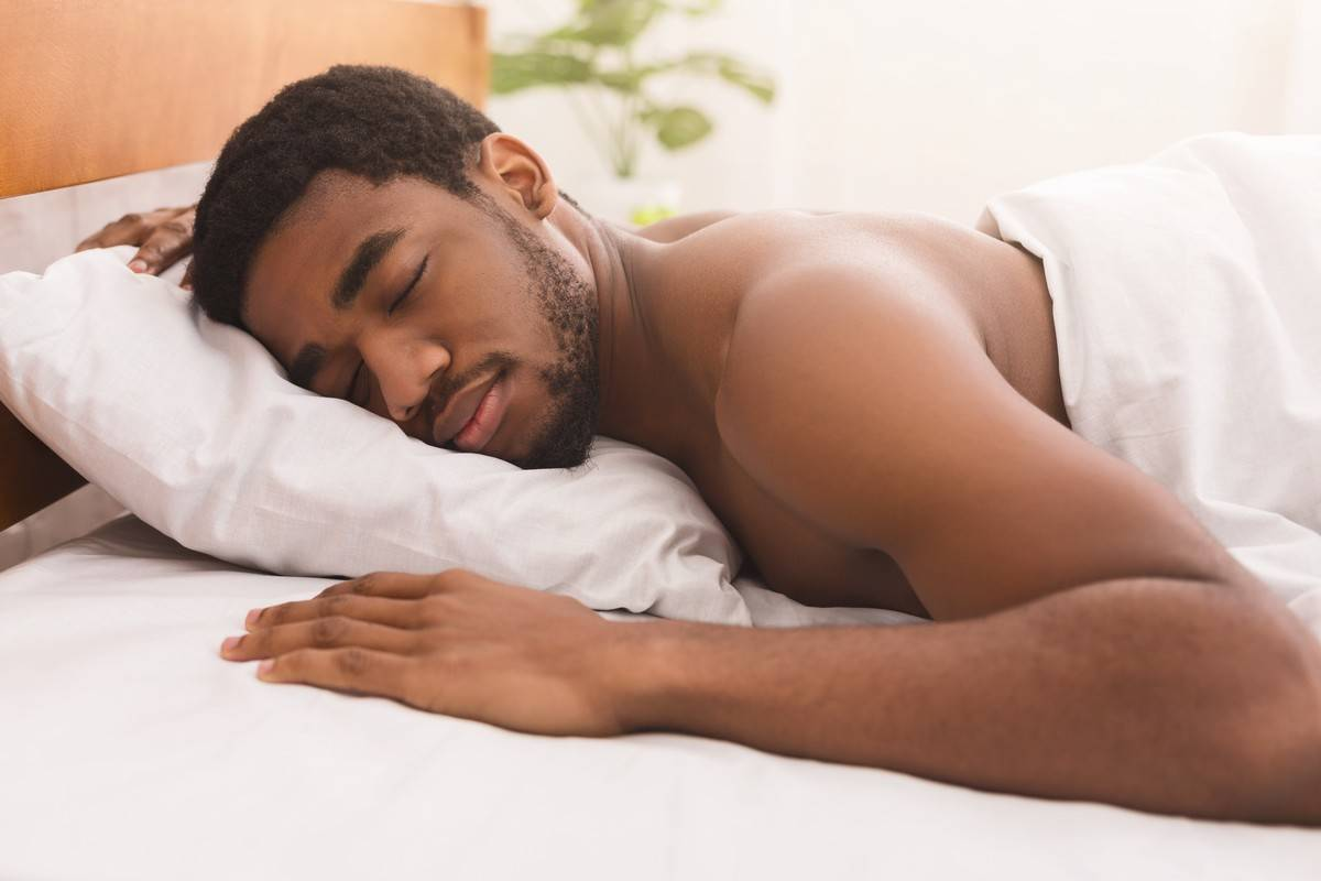 A man sleeps on his stomach in bed.