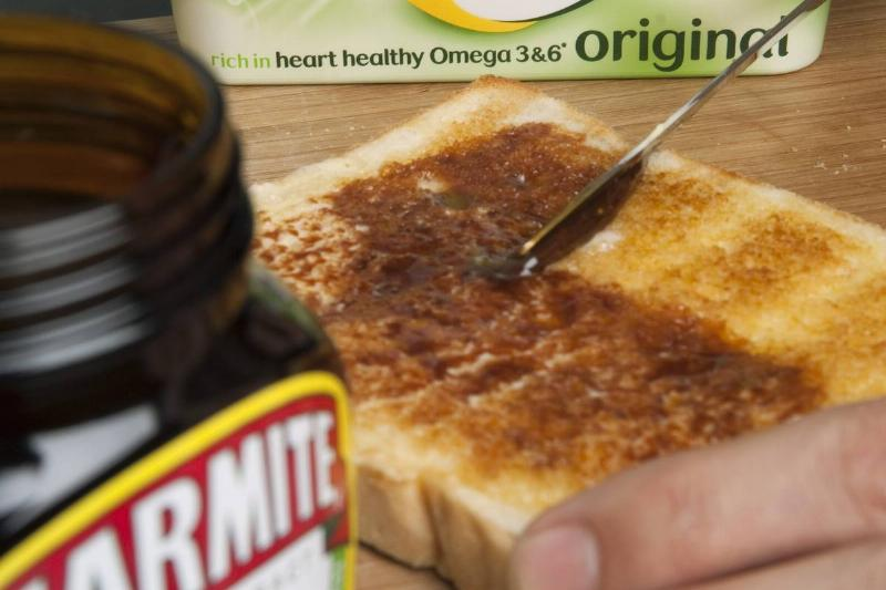 A person spreads marmite on white toast.