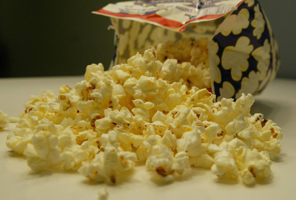 Cheese-flavored popcorn pours out of a microwavable bag.