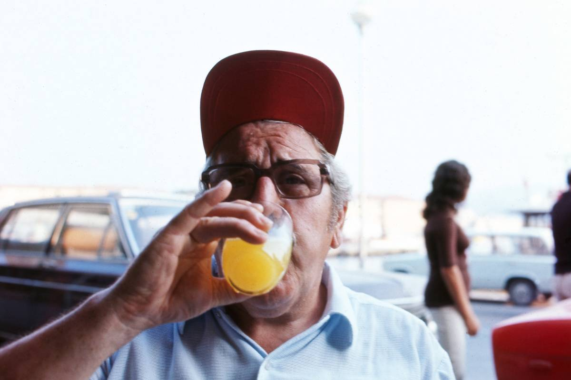 A man drinks a glass of orange juice.