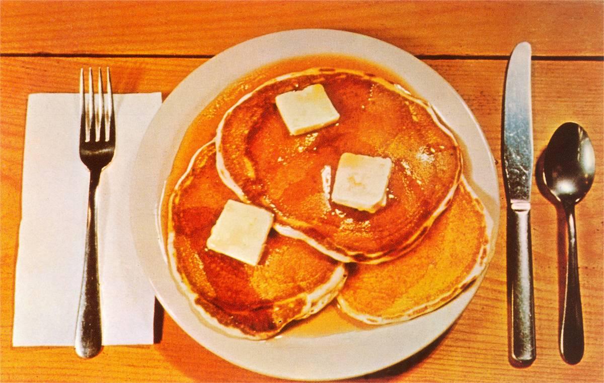 A vintage color photograph shows pancakes on a place setting.