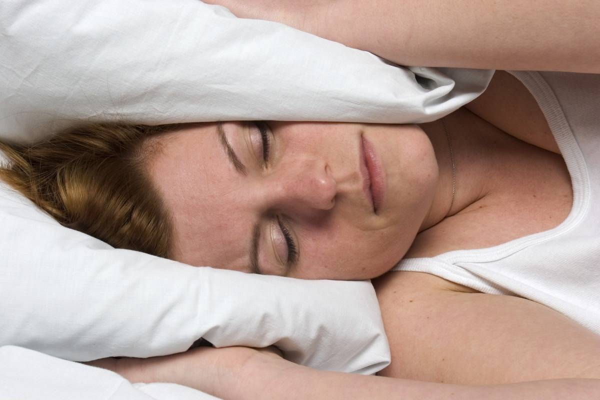 A woman holds her pillow around both ears as she tries to sleep.