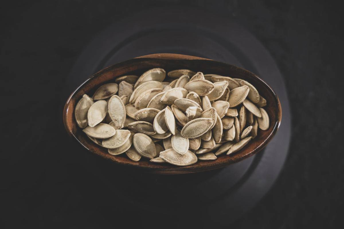 Pumpkin seeds are stored in an oval container.