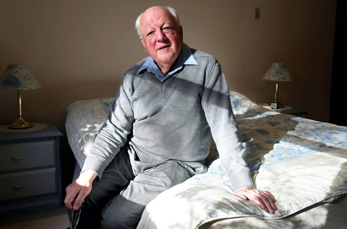 An elderly man who suffers from sleep disorders sits up in bed.