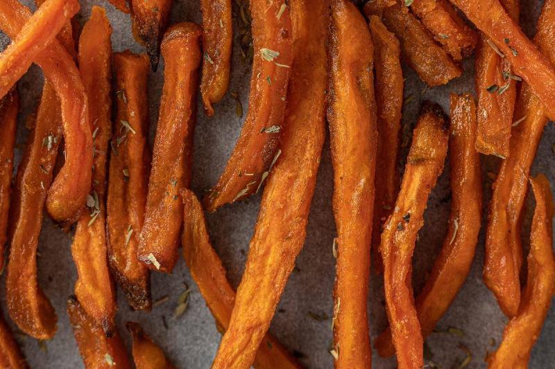 Sweet potato fries are arranged on a baking pan.