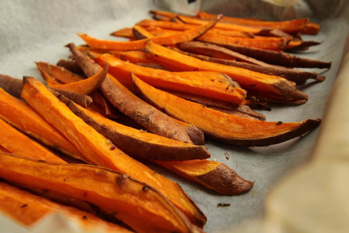 Sliced sweet potato fries are laid out on a baking sheet.