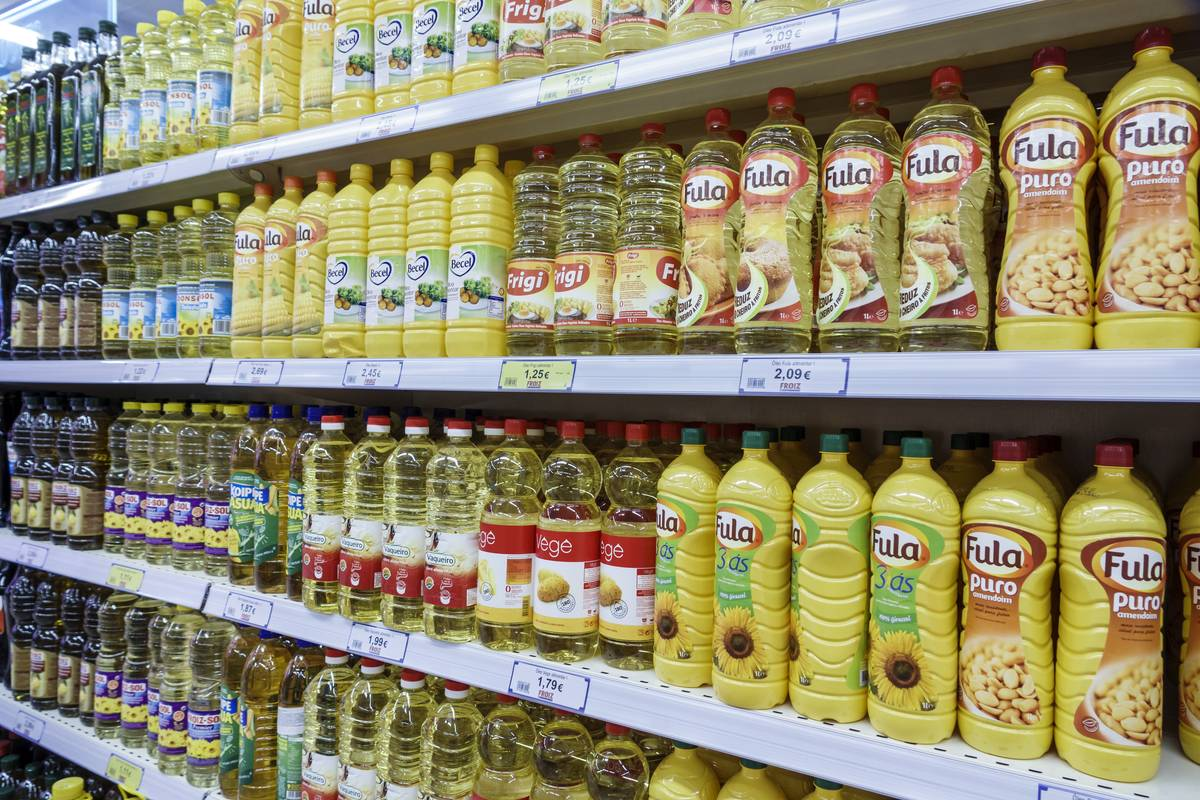 A grocery store shelf is filled with vegetable oils.