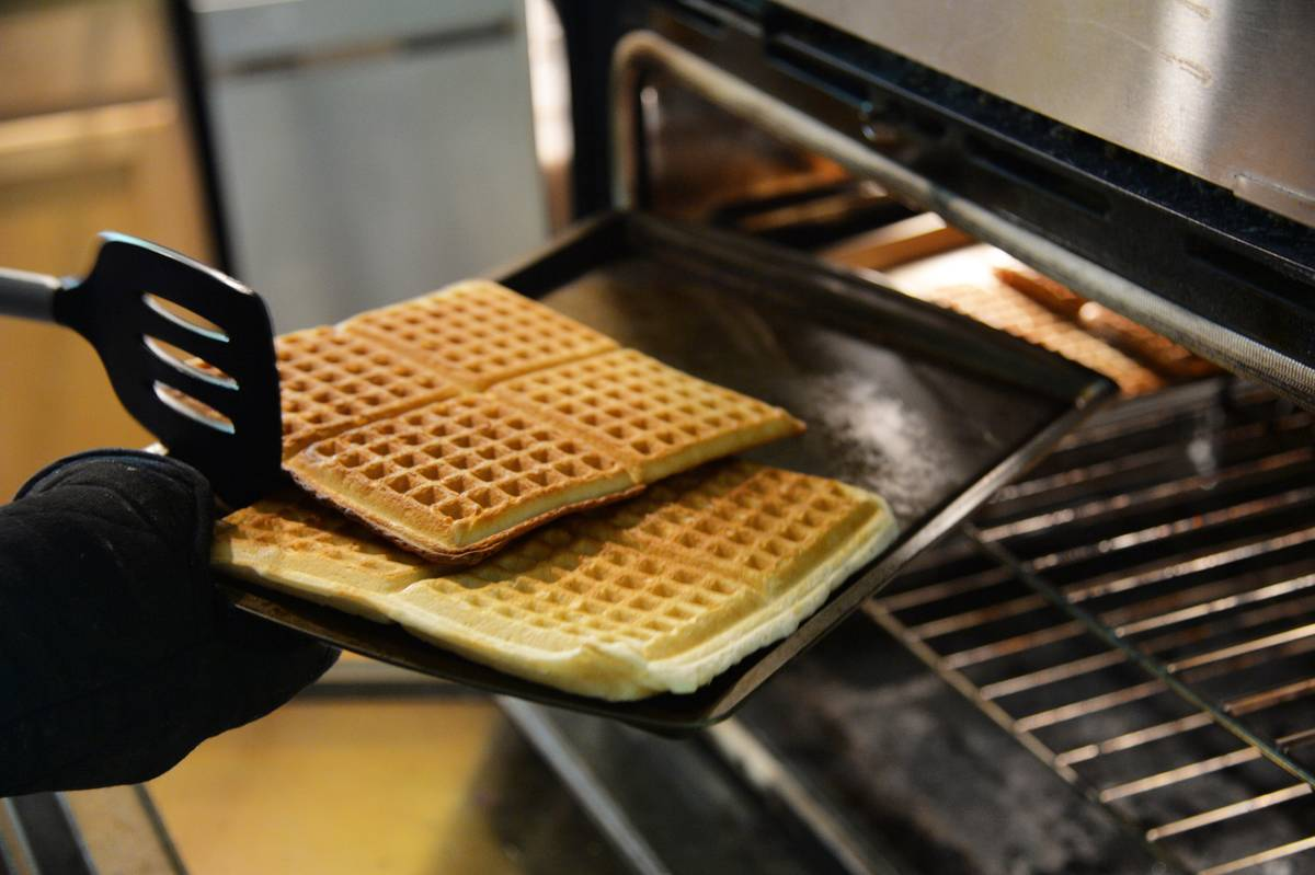 A chef takes Belgian waffles out of an oven.