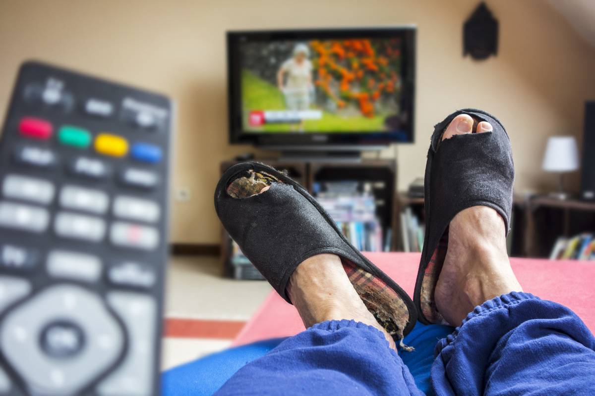 A man lies on the couch while watching TV.