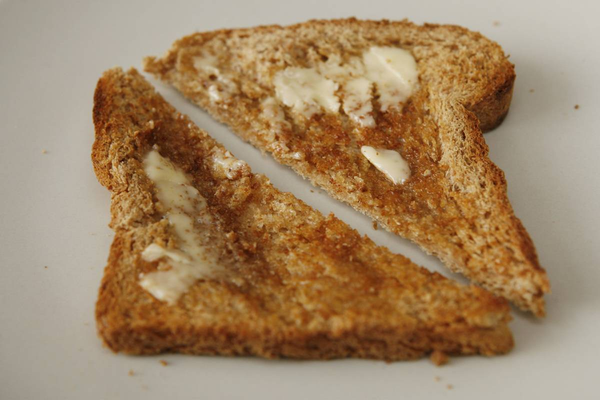 Two slices of whole grain toast have butter.