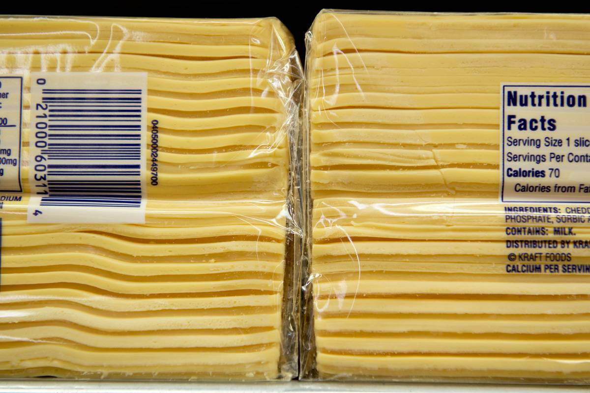 Packages of stacked American cheese slices are wrapped in plastic and have a nutrition label.