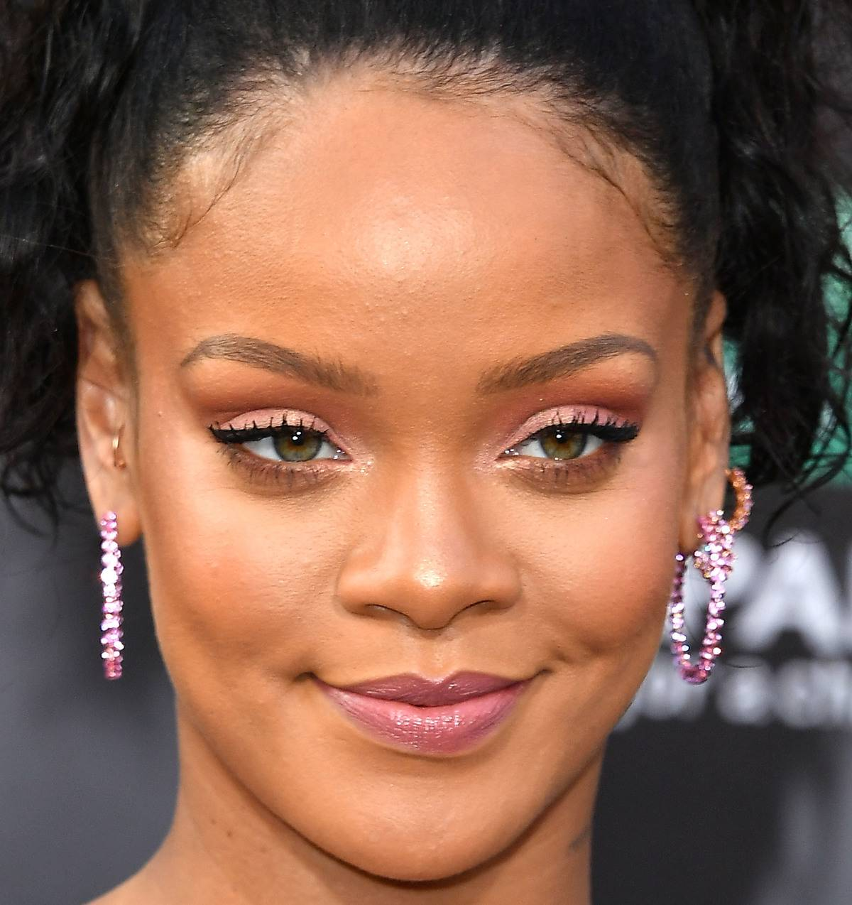 A close-up shows Rihanna's face with makeup on.