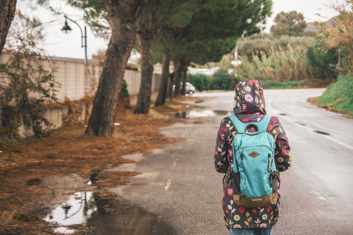 In the rain, a person walks down the street with a backpack.