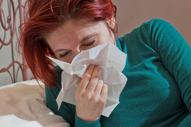 A girl with a cold sits up in her bed and blows her nose.