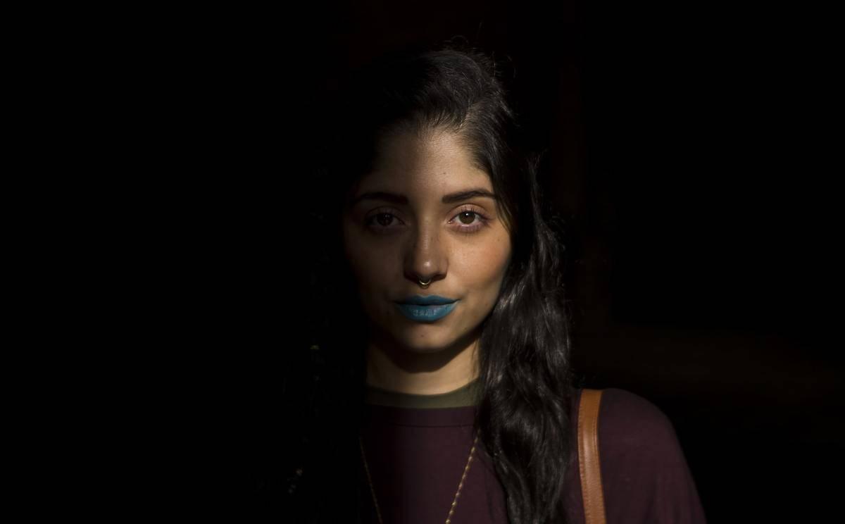 A woman in the dark wears blue lipstick.