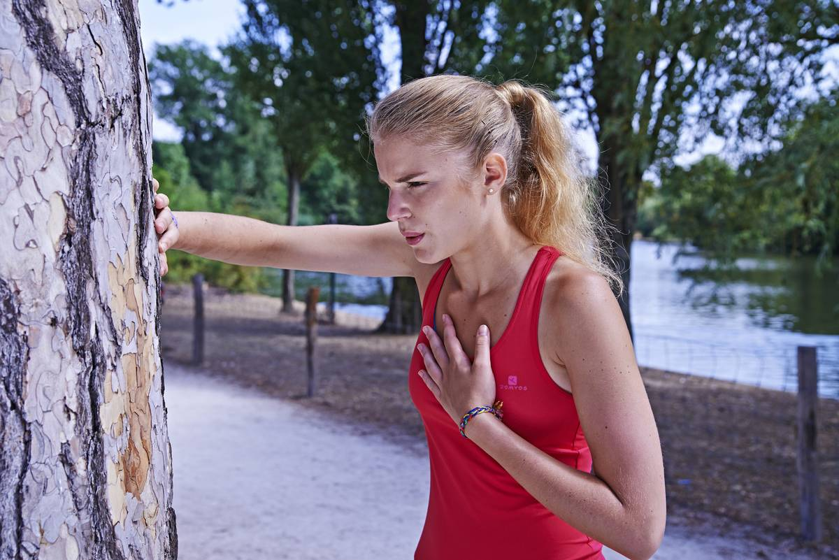 A woman rests against a tree while she catches her breath from jogging.