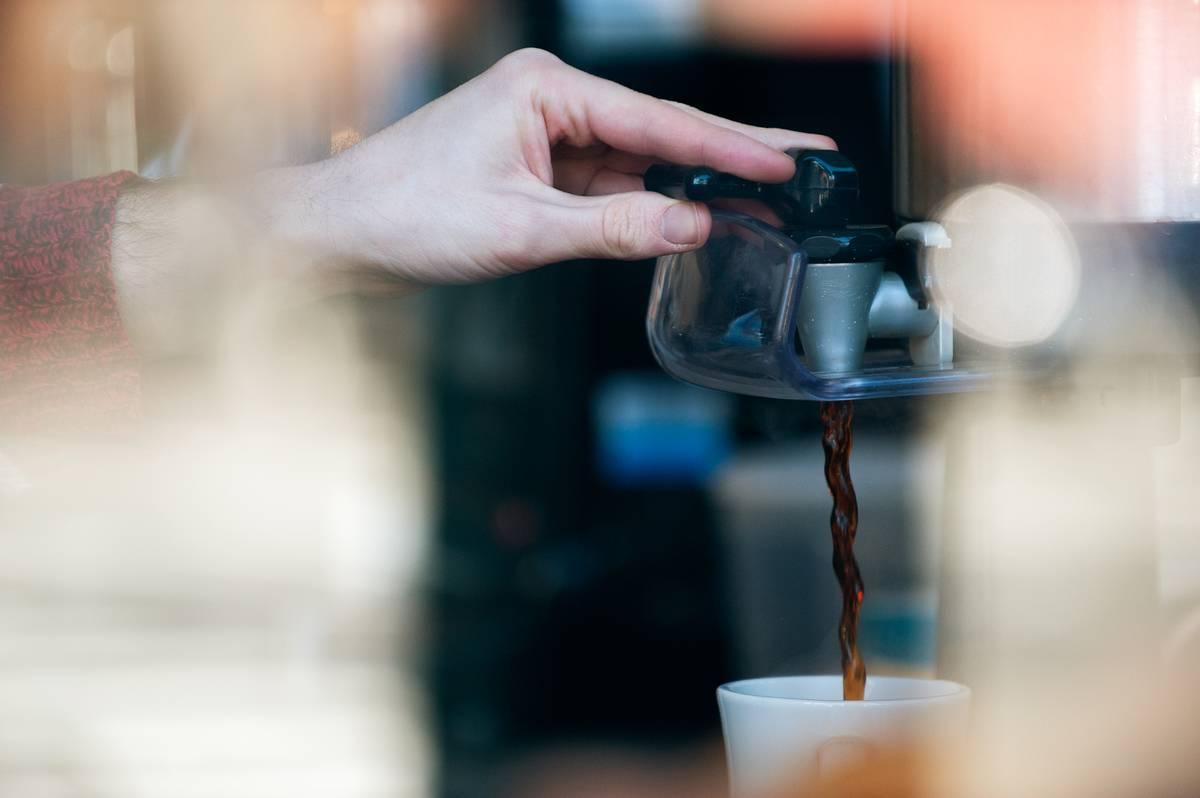 A person brews coffee.