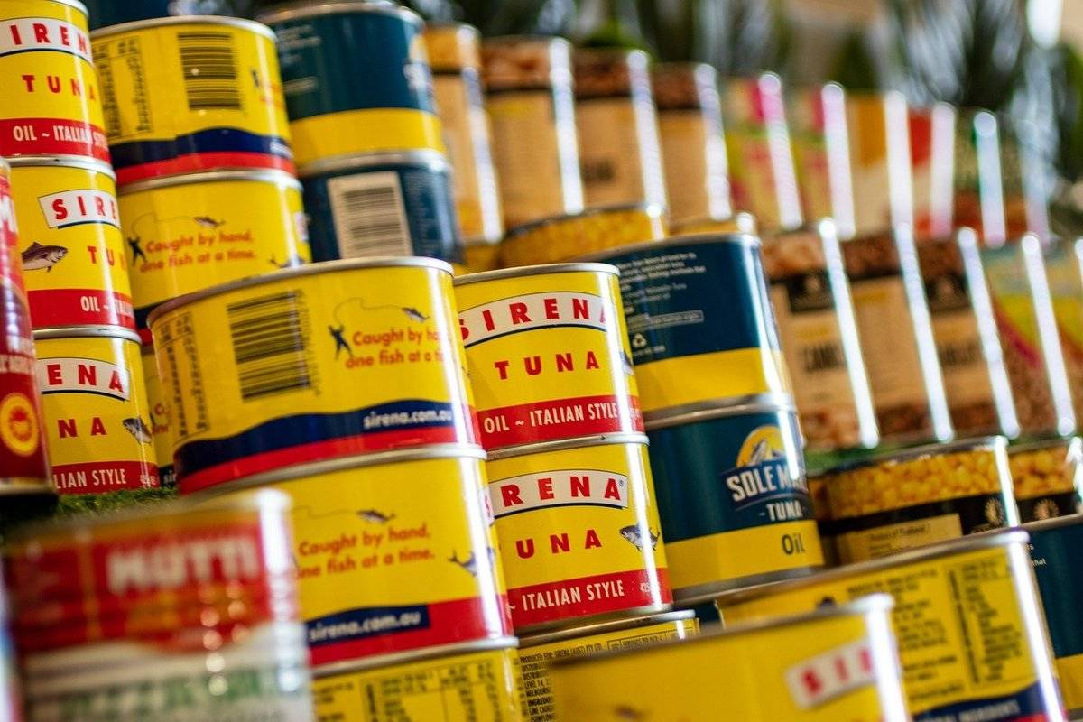 Cans of tuna are stacked at a supermarket.