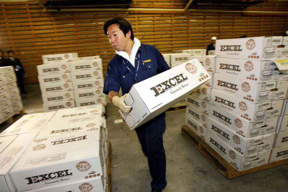 A shipping company employee carries a box in a warehouse.