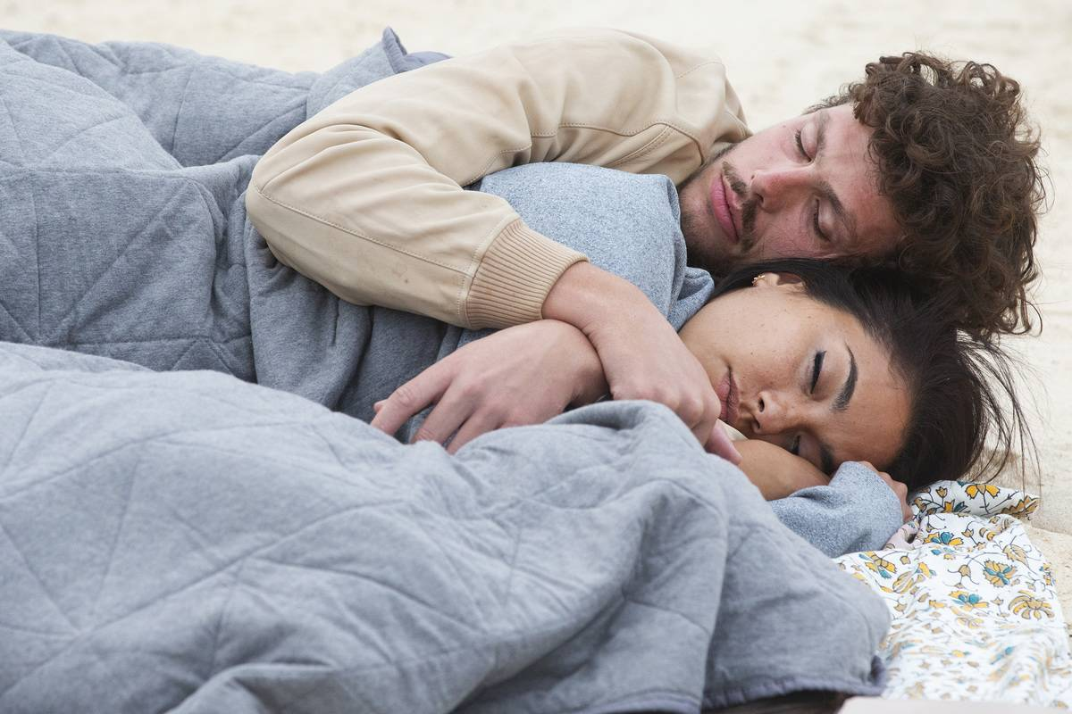 A couple sleeps together on a beach.