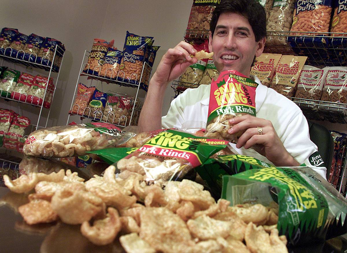 A man eats from a bag of pork rinds.
