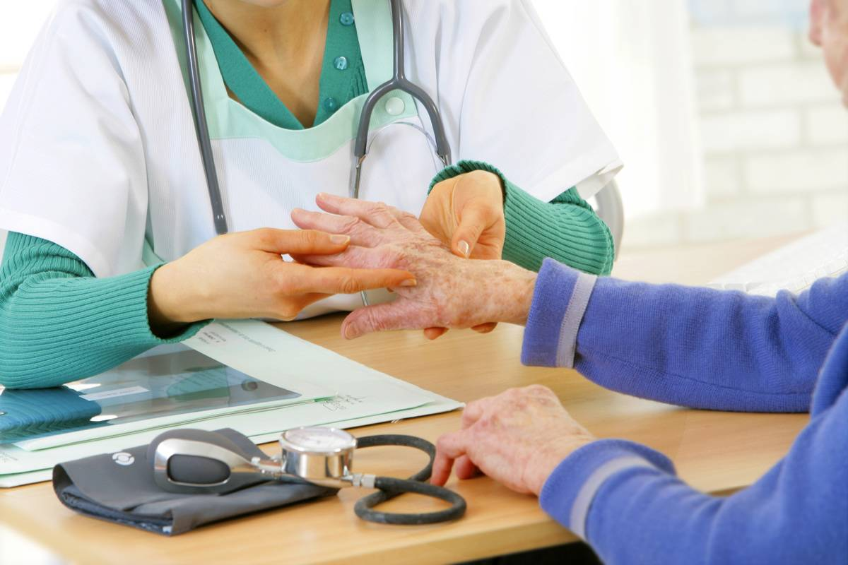 A doctor examines an elderly woman's hands.