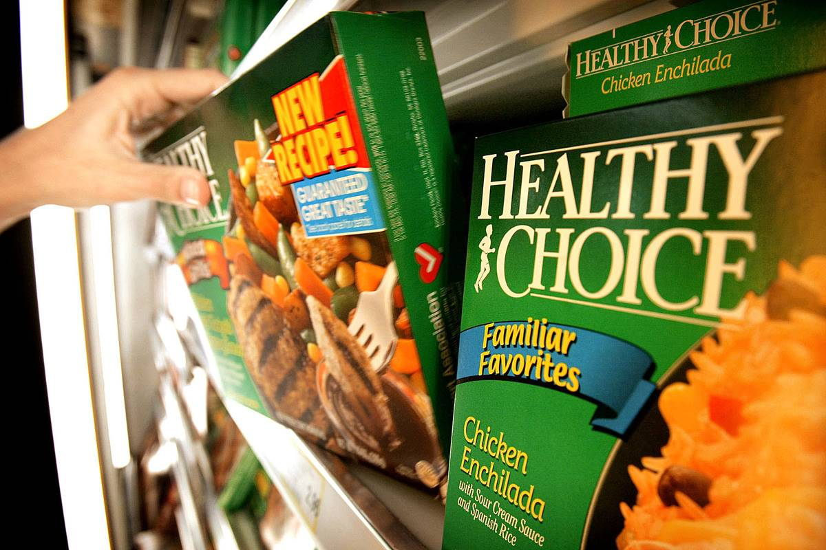 A person pulls a Healthy Choice frozen dinner from a grocery store shelf.