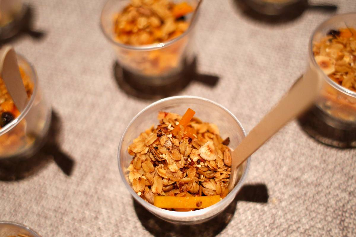 Granola is offered in small sample cups with wooden spoons.