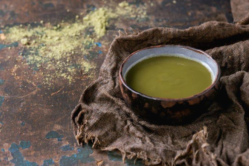 Ceramic cup of green matcha tea on wet sackcloth rag over dark wooden textured background