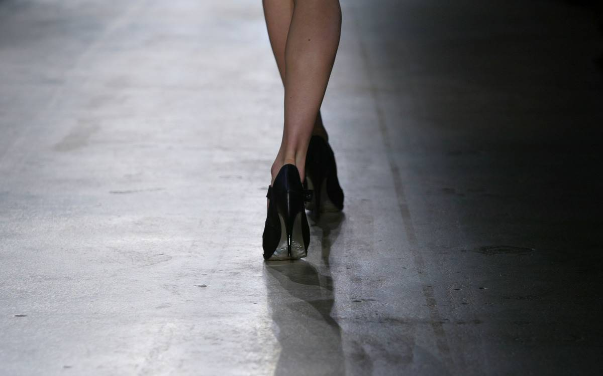 A model walks down a runway with high heels.