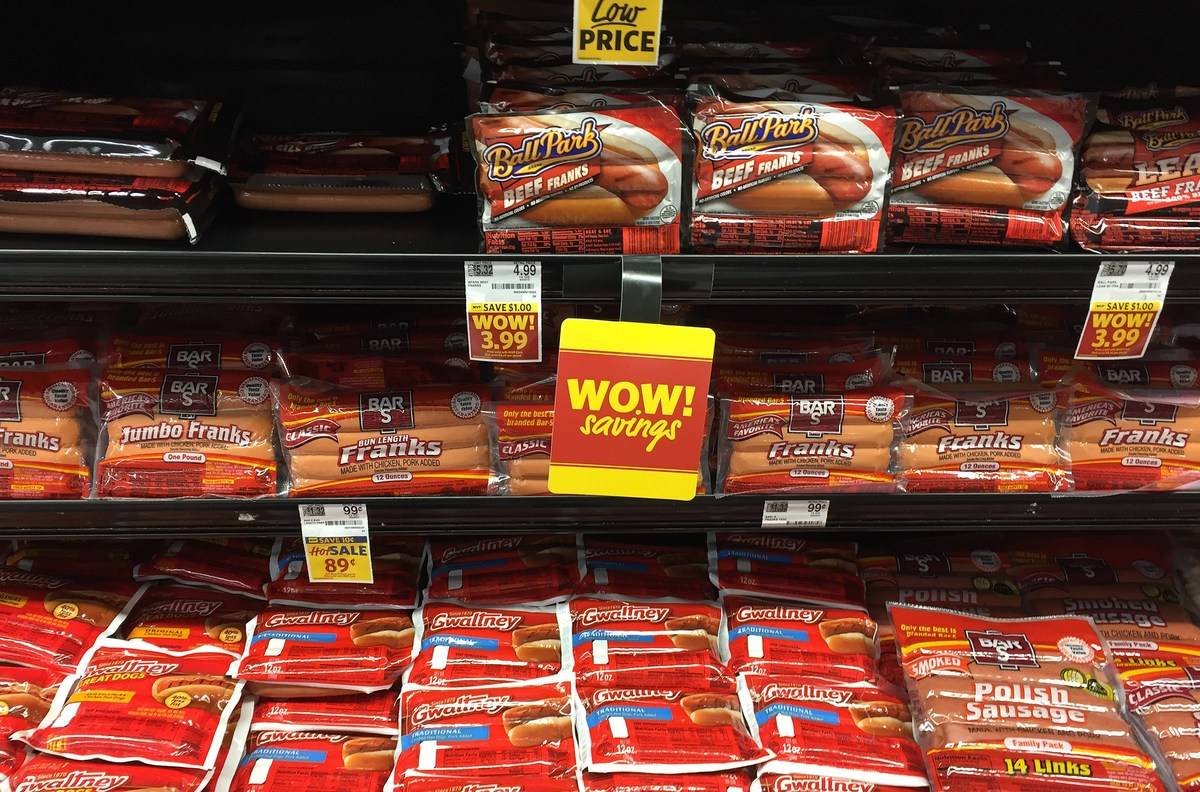 Hot dogs line grocery store refrigerator shelves.